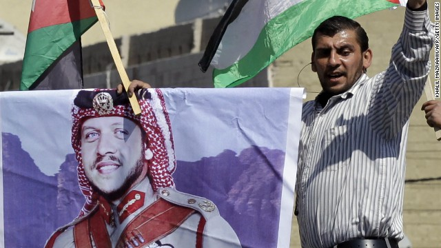 A pro-government protestor holds a banner picturing King Abdullah during a demonstration after Friday prayers in Amman on March 23, 2012.