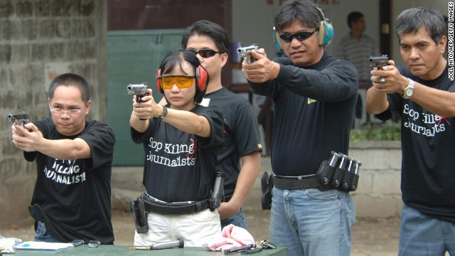 Journalists learn to shoot pistols in Manila in 2005 as part of an advocacy group's campaign to curb attacks against the media in the Philippines by arming reporters.
