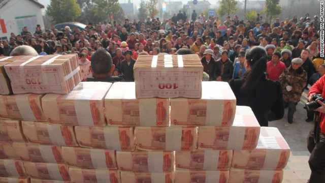 Villagers stand in front of a 'money wall' in Sichuan, China waiting to collect their year-end bonus from their investments on 14 January.