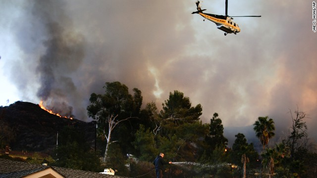 A helicopter carrying water flies over a burning residential area in Azusa, California, as a man sprays water on his home January <a href=