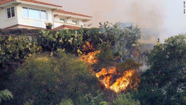 The fire makes it way up a hill toward a house in Glendora on January 16.