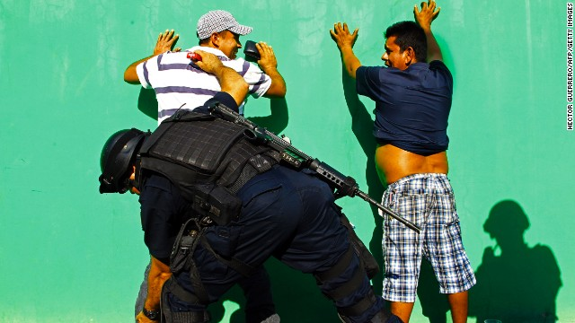 Mexican federal police check men in the streets of Apatzingan on Wednesday, January 15. Some vigilante groups have vowed not to hand over their guns until cartel leaders are captured.