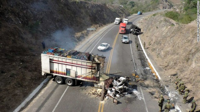 Mexican soldiers stand next to a truck burned by members of an armed group on a road in Michoacan state on Sunday, January 12. Some residents say they're caught in the middle of spiraling violence that shows no sign of slowing.