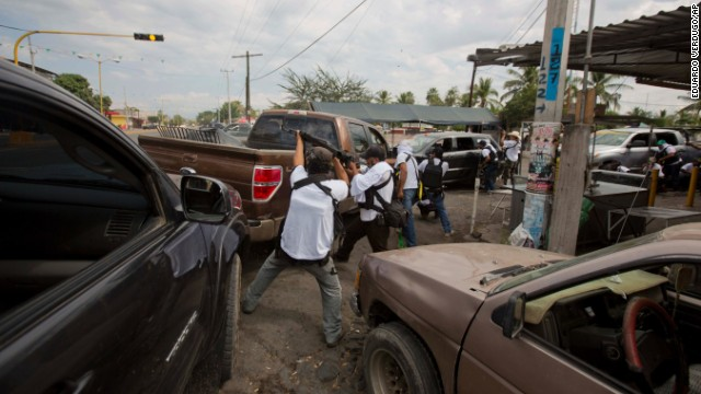 Men from a self-defense group engage in a firefight to flush out alleged members of the Knights Templar drug cartel from Nueva Italia on January 12. Critics suggest the vigilante groups contain some criminals from rival gangs who are using them as a means to win more territory.