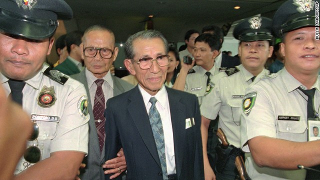 Police escort Onoda shortly upon his arrival in Manila in May 1996. He was a controversial figure in the Philippines, where anger remained over the Japanese occupation. The Philippine government pardoned him, but relatives of people he was accused of killing gathered to demand compensation when he returned to Lubang.