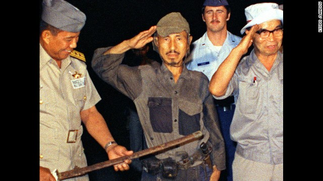 <a href='http://www.cnn.com/2014/01/17/world/asia/japan-philippines-ww2-soldier-dies/index.html'>Hiroo Onoda</a>, center, salutes after handing over his military sword on Lubang Island in the Philippines in March 1974. Onoda, a former intelligence officer in the Japanese army, had remained on the island for nearly 30 years, refusing to believe his country had surrendered in World War II. He died at a Tokyo hospital on January 16. He was 91.