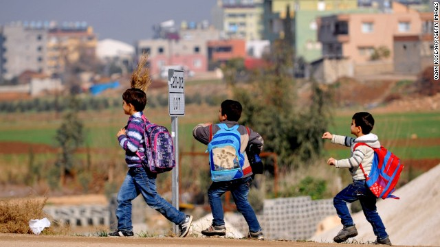 Syrian children walk on the street after attending school on January 18 in Hatay, Turkey.