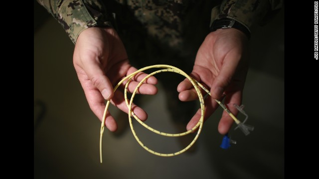 A military doctor holds a feeding tube used to feed detainees on a hunger strike at a Camp Delta hospital at Guantanamo in June 2013. In March 2013, the U.S. military announced that dozens of detainees had begun a hunger strike. By that June, more than 100 detainees were on a hunger strike, and more than 40 were being force-fed, military officials said.
