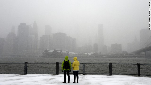 Snow falls as tourists take in the New York skyline from the Brooklyn Bridge Park on January 21.
