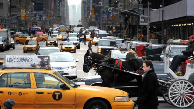 A horse pulls a carriage between cars and cabs along 59th Street in January.