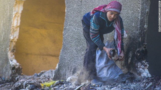 A Syrian child collects items from a garbage pile on Saturday, January 18, in Douma, northeast of the capital.