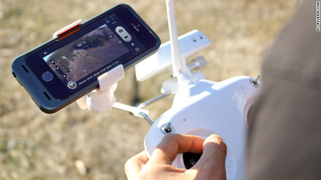 Live video from a DJI Phantom drone is displayed on an iPhone app. The Phantom controller has a special mount for the smartphone.