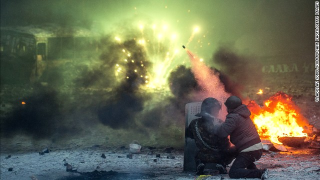 Protesters shoot from behind a shield among burning automobile tires in Kiev on January 22.