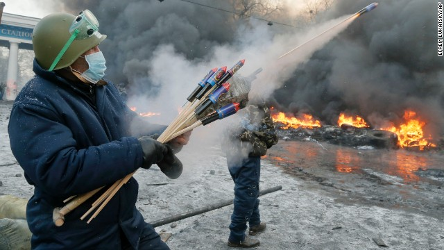 A protester shoots fireworks at police during clashes in Kiev on January 23.