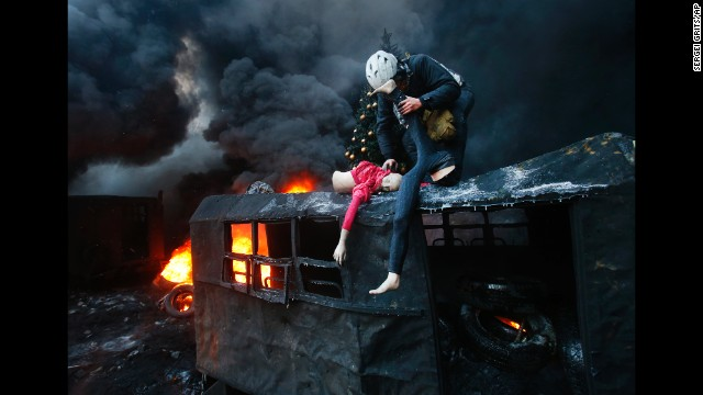 A protester pulls apart a mannequin on the roof of a burnt-out truck during clashes in Kiev on January 23.