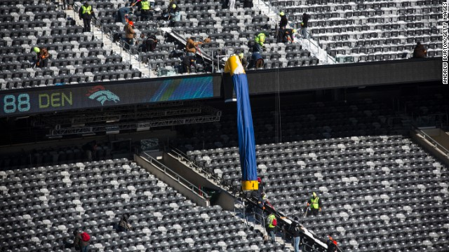 Workers remove snow from the stands. Cold-weather welcome kits have been produced for fans. They will include earmuffs, hats, mittens and lip balm, among other items.