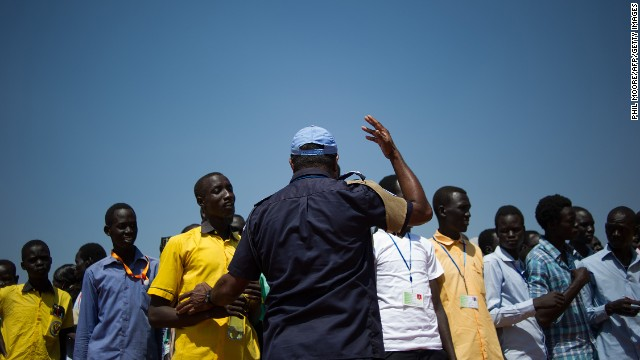 A United Nations peacekeeper gestures as South Sudanese students wait to walk back to a camp for internally displaced people after taking an English exam at a United Nations base in Juba, South Sudan, on Monday, January 13.
