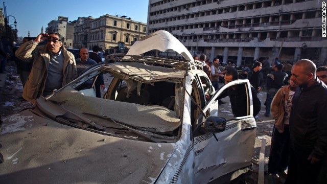 People inspect a destroyed taxi at the site of the explosion.