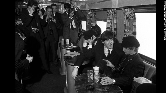 The Beatles have their pictures taken as they sit on a train taking them from New York to Washington on February 11, 1964.