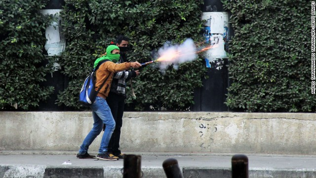 A Muslim Brotherhood supporter aims fireworks at pro-military demonstrators clashes in Cairo.