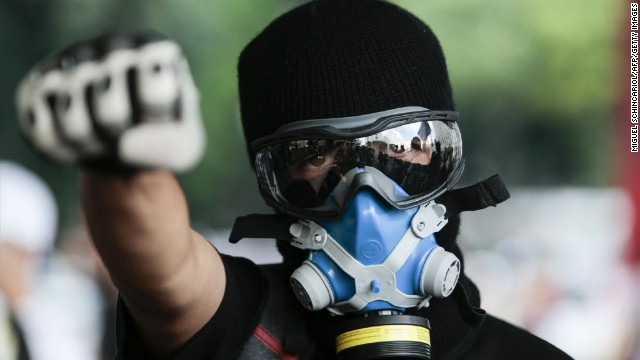 A man wearing a gas mask participates in the protest.