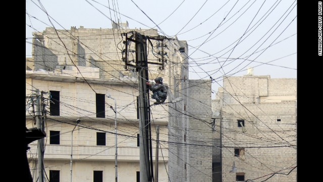 A man tries to fix electrical wires in Aleppo on January 27.