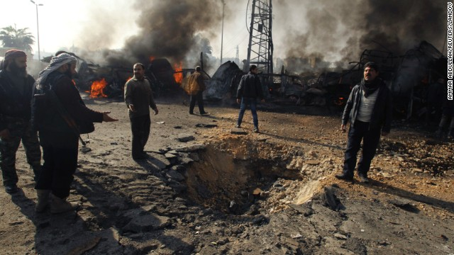Rebels and civilians check out a crater that activists say resulted from a Syrian government airstrike on an Aleppo bus station on Tuesday, January 21.