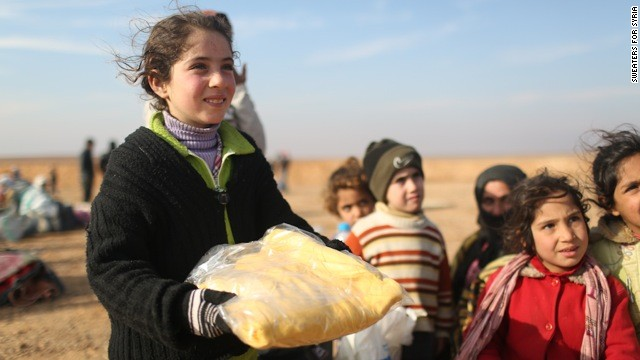 Syrian refugee Hala had been on the road for two days when she arrived in Jordan. She smiles at Sweaters for Syria volunteers handing out winter clothes.