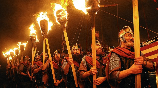 "In Lerwick, a so-called ""guiser squad"" of bearded and armored gents (shown here in a previous Up Helly Aa) is led in a torchlit procession by the ""jarl,"" their leader."