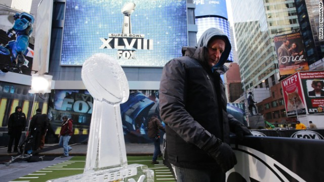 A worker in Times Square moves a barrier January 28 near an ice sculpture that is modeled after the Lombardi Trophy.