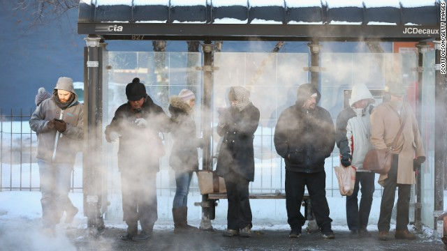 With temperatures around -10 degrees, commuters wait for a bus in Chicago on January 27.