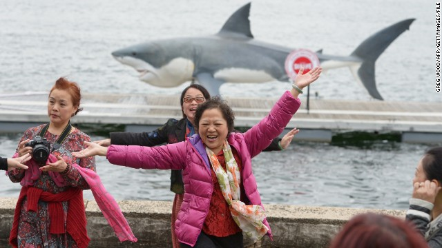 Chinese tourists pose for photographs as a gigantic Great White Shark replica