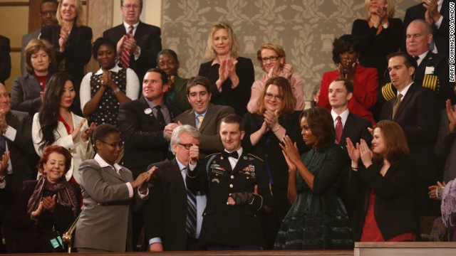 US Army Ranger Sgt. First Class Cory Remsburg, injured while serving in Afghanistan, acknowledges the crowd during a standing ovation for him as President Barack Obama delivers his State of the Union speech.