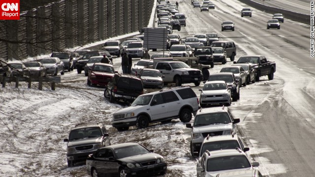 "As of Wednesday afternoon, hundreds of cars were still stranded on Atlanta's interstates, as seen in this photo taken on a GA 400 exit by iReporter Dylan Wintersteen. ""It's bizarre to see all the cars people abandoned and just left last night,"" he said."