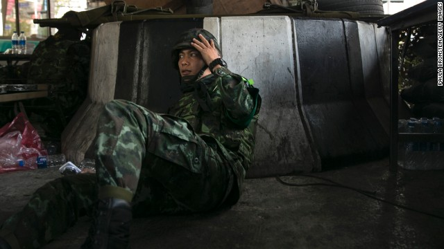 A soldier takes cover as violence escalates before the elections on February 1.
