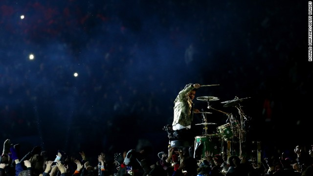 Fans surround Mars as he performs a drum solo to start the show.