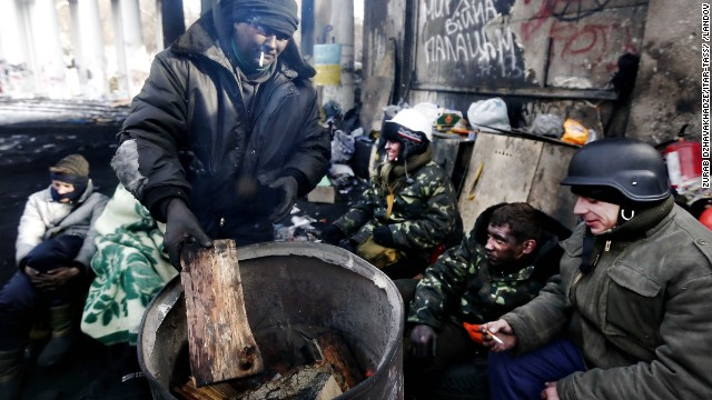 Opposition supporters warm themselves in Kiev on Saturday, February 1.