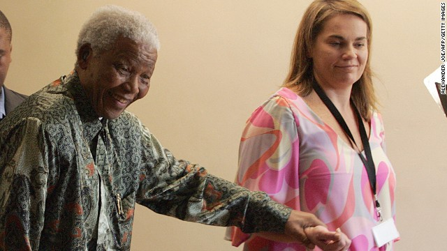 In this file photo, Nelson Mandela leaves his office in Johannesburg with Mandela Rhodes Foundation spokeswoman Zelda la Grange. Nine former staffers, including Le Grange, will receive 50,000 rand each.
