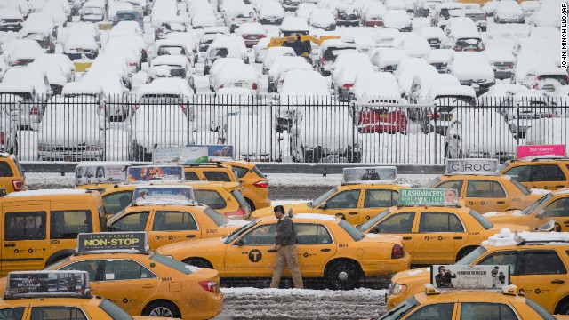 A taxi driver walks beside his vehicle in the parking lot of Terminal B at LaGuardia Airport on February 3.