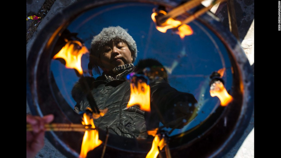 A worshipper burns incense at a temple in Beijing on Tuesday, February 4. Millions of people around the world, predominantly those of Chinese descent, are ushering in the Year of the Horse during Lunar New Year celebrations.
