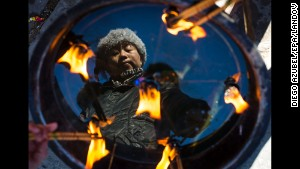 A woman is reflected in a basin as she lights incense at a temple in Beijing on Tuesday, February 4.