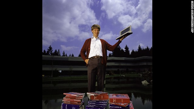 Gates poses outdoors with Microsoft's first laptop in 1986 at the new 40-acre corporate campus in Redmond, Washington. In March 1986, Microsoft held an initial public offering of 2.5 million shares. By the end of the year, Gates became a billionaire at the age of 31. Microsoft was the first company to dominate the personal computer market with its MS-DOS system and subsequently the Windows platform.