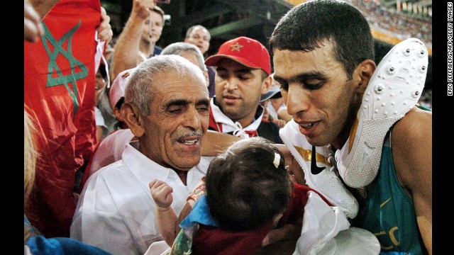 Moroccan runner Hicham El Guerrouj, right, smiles at his baby daughter, Hiba, next to his father, El Ayachi, at the 2004 Olympic Games in Greece.