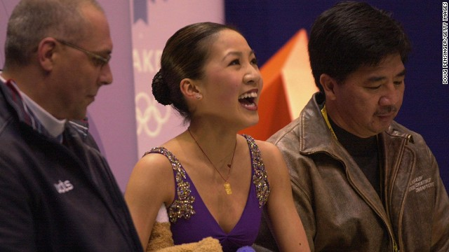 U.S. figure skater Michelle Kwan smiles to the crowd after competing during the 2002 Olympic Games in Salt Lake City. At right is her father, Danny.