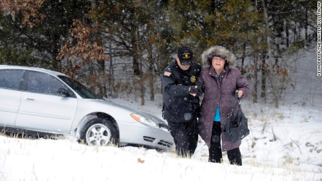 Lt. Rick Lucy of the Baxter County Sheriff's Office helps Donna Mullaney up an embankment in Mountain Home, Arkansas, after she lost control of her vehicle on an icy road February 4.