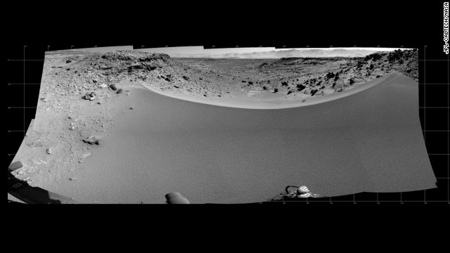 "This mosaic of images from the Navigation Camera on Curiosity shows the terrain to the west from the rover's position on the 528th Martian day, or sol, of the mission on January 30. The images were taken right after Curiosity had arrived at the eastern edge of a location called ""Dingo Gap."" A dune across the gap is about 3 feet high in the middle and tapered at south and north ends onto low scarps on either side of the gap. The rover team is evaluating possible driving routes on the other side before a decision whether to cross the gap. The view covers a panorama from south, at the left edge, to north-northwest at the right edge. It is presented as a cylindrical projection."