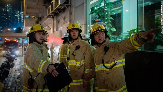 Firefighters appear near the site where an apparent bomb was discovered Thursday in Hong Kong.