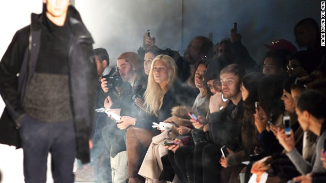 Audience members in the front row look on as a model displays a look by Nautica.