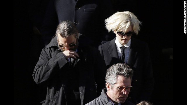 "Actor Joaquin Phoenix, left, exits the church. Phoenix appeared with Hoffman in ""The Master."""