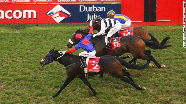 Khumalo, seen here in the foreground, rides his mount Heavy Metal to victory in the Durban July at Greyville Racecourse in July 2013.